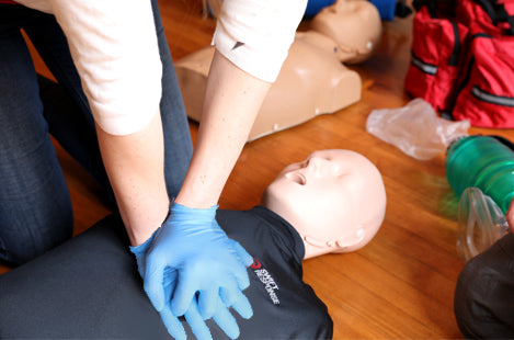 girl with gloves on doing CPR