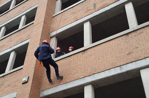 Rescuer rappelling during rope rescue training course