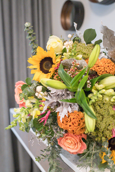 Vibrant shades bouquet of sunflowers, lilies and roses
