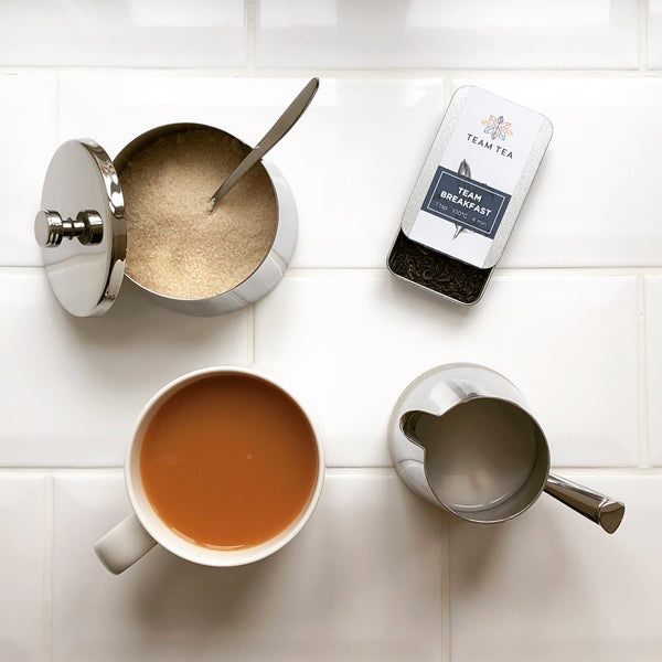 A mug of English breakfast tea, brewed with loose leaves. Along with the mug is a tin of loose leaf tea, a pot of sugar and a jug of milk. The background is white tiles.
