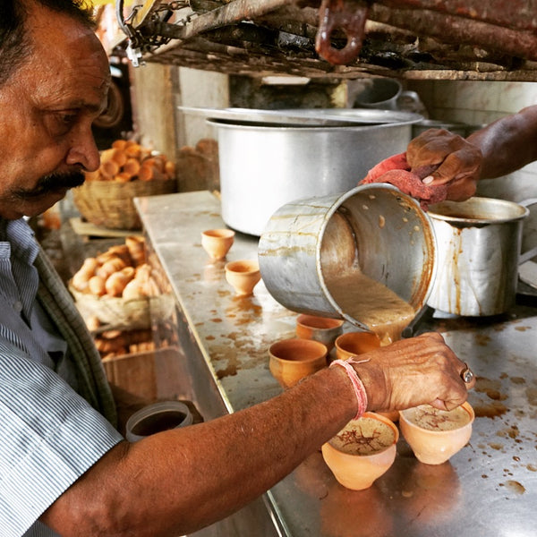 Cups of Chai tea being poured out in Kolkata, India. A very large pan that's being used to make chai is in the background, with a man helping to pour the tea in the foreground.
