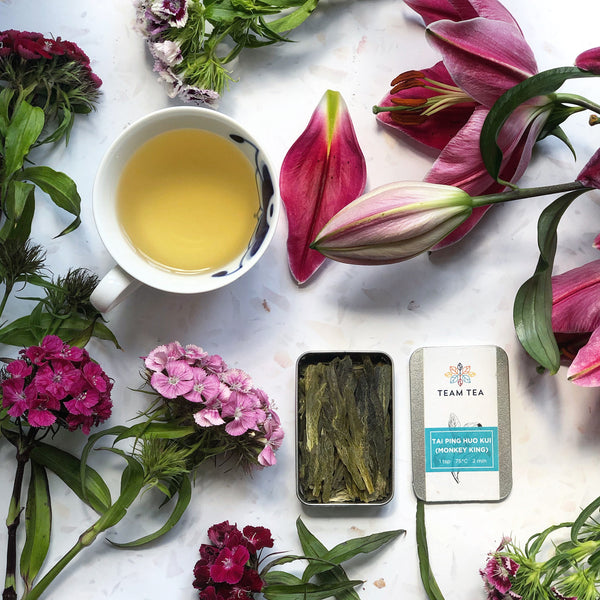 A cup of freshly brewed loose leaf tea, sat alongside an open tin of Team Tea's Tai Ping tea. The scene is beautiful set with a surrounding of fresh flowers.