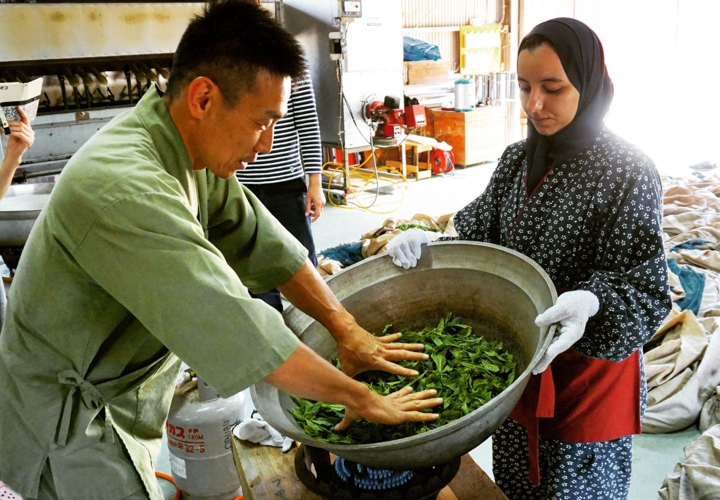 A photo showing two people panning some tea leaves.