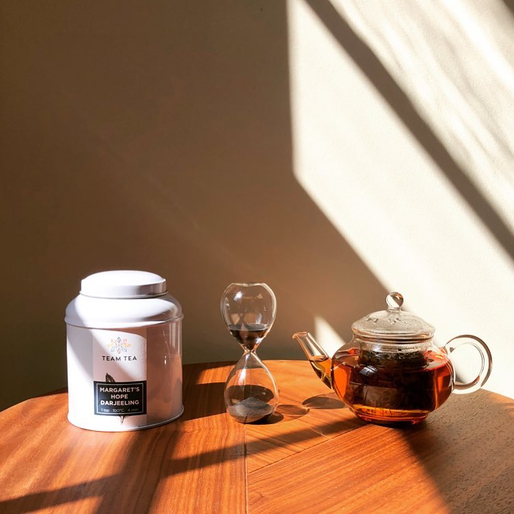 A pot of loose leaf tea, along with one of Team Tea's loose leaf tins and an hourglass timer.