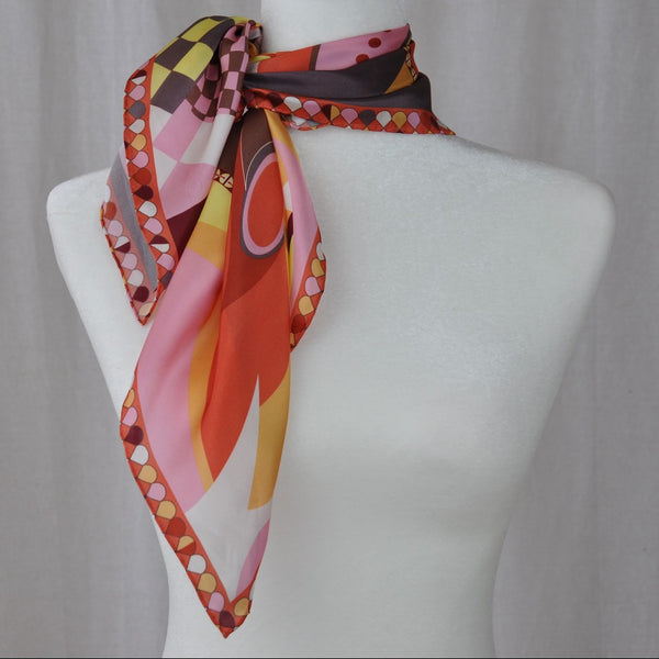 Orange dominates this abstract silk scarf. Brown, pink, and yellow compliment the blue. Wear it with casual clothes or with a work outfit.