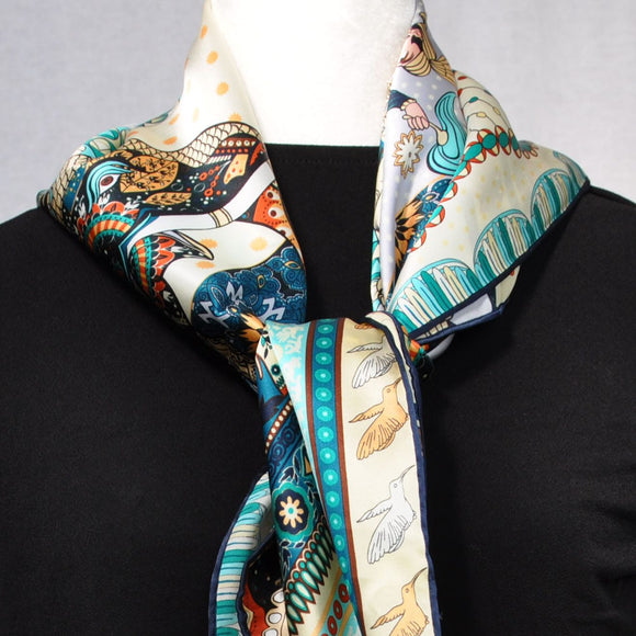 Beige, blue, and teal dominate this silk scarf.  Add a wonderful splash of teal to outfits.