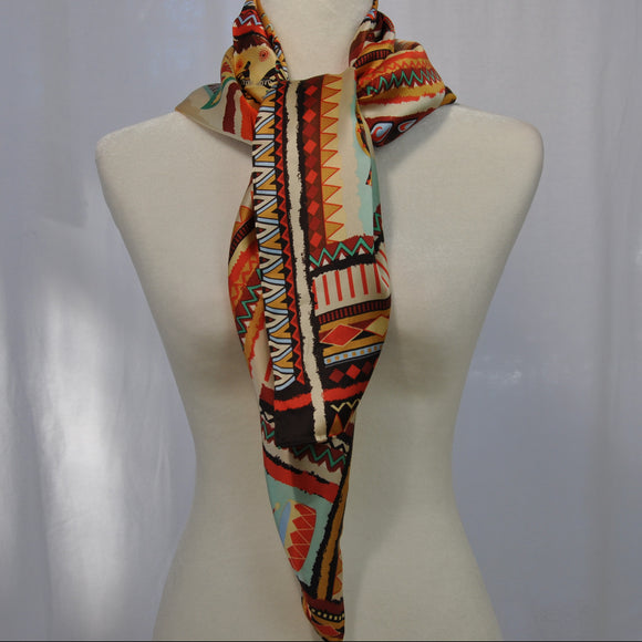 Beige silk scarf with a bit of orange to highlight the other hues is a nice accent for work for an evening out.