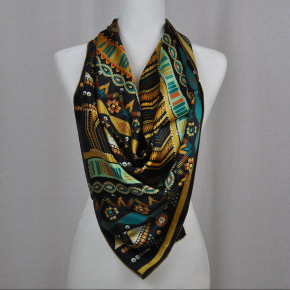 There are both warm and cools colors in this navy mix Aztèque style silk scarf so you can wear it with many different colored outfits.