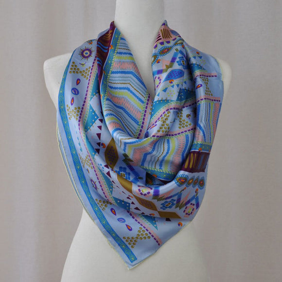 There are both warm and cools colors in this Aztèque style silk scarf so you can wear it with many different colored outfits.