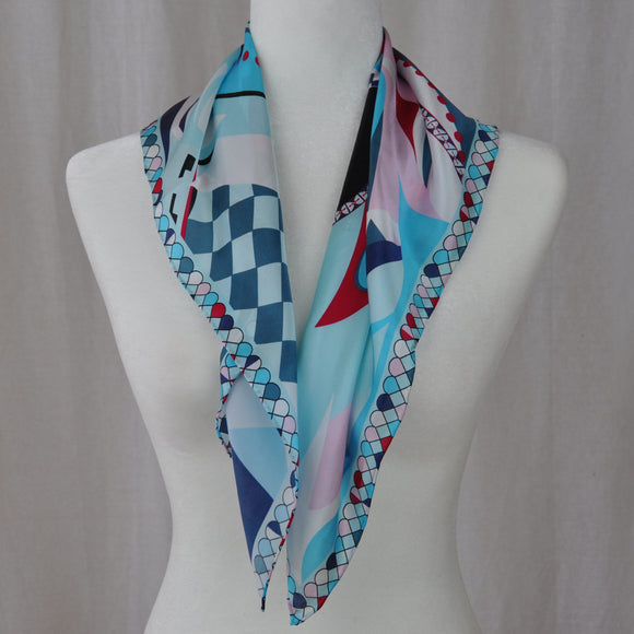 Blue dominates this abstract silk scarf. Navy, rose, and red compliment the blue. Wear it with casual clothes or with a work outfit.