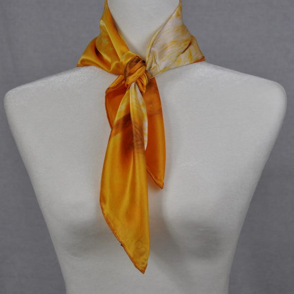 An orange floral silk scarf portraying brown dried flowers. Wear this orange silk scarf to brighten up a white dress.