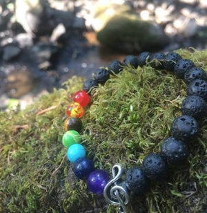 Colored lava stone & bead music bracelet on a green mossy rock by stream of water and rocks with silver treble clef.