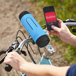 Blue portable bike mounted speaker flashlight on a bike with a person who is holding a phone.