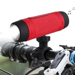 Red portable bike mounted speaker flashlight turned on to shine light on a bike.