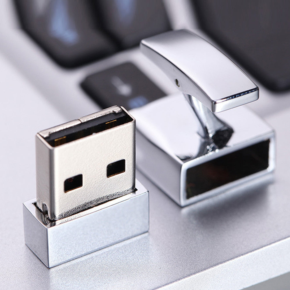Silver cuff-link USB memory card open on a light gray table in front of a computer.