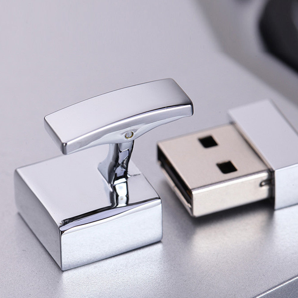 Silver cuff-link USB memory card open on a light gray table.