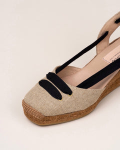 Linen espadrilles with medium wedges style. Closed at the toe, with black ribbon detail on top. Tie-up knotted at the ankle. Natural leather cousin insole.   Height: 1,5 inch wedge heel. Perfect for comfy walking.