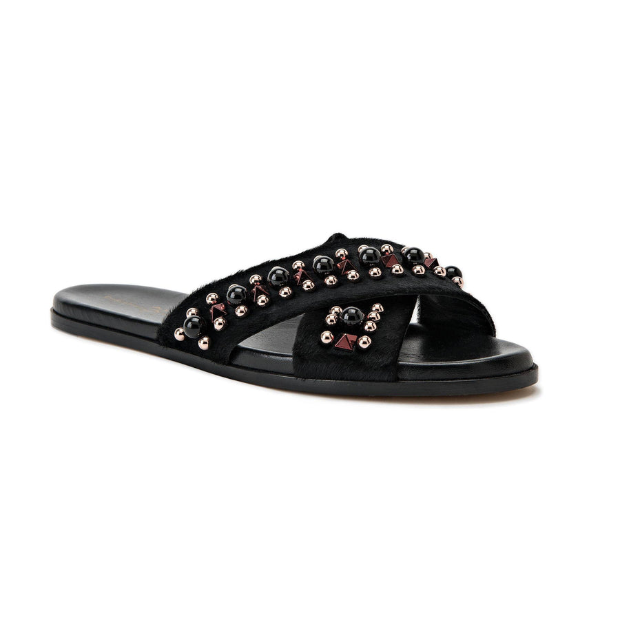 Profile of Aria black pony hair slide sandal with custom hardware accents and a black sole