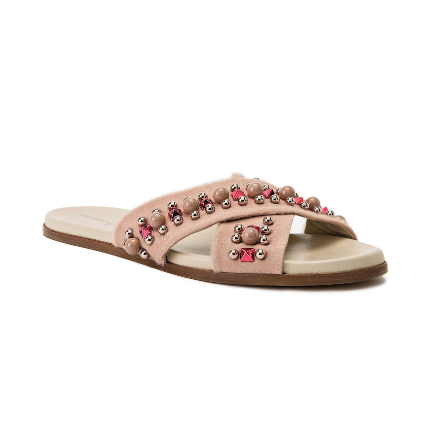 Profile of Aria nude pony hair slide sandal with custom hardware accents and a nude sole