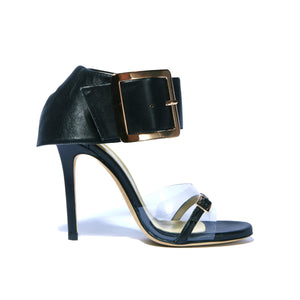 Side of Neeka black leather heel with clear strap across foot with large buckle enclosed ankle wrap