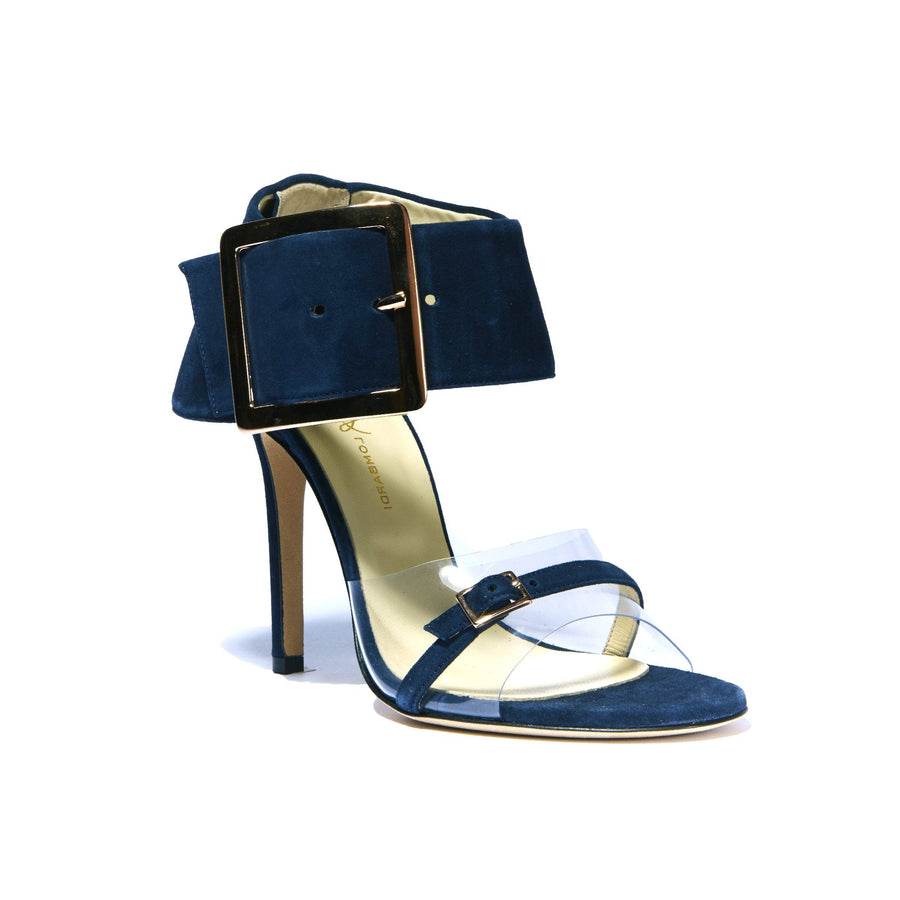 Profile of Neeka navy suede heel with clear strap across foot with large buckle enclosed ankle wrap