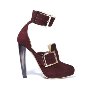 Profile of Ronnie bacco suede boot with a horn heel and large buckle accents around ankle and foot