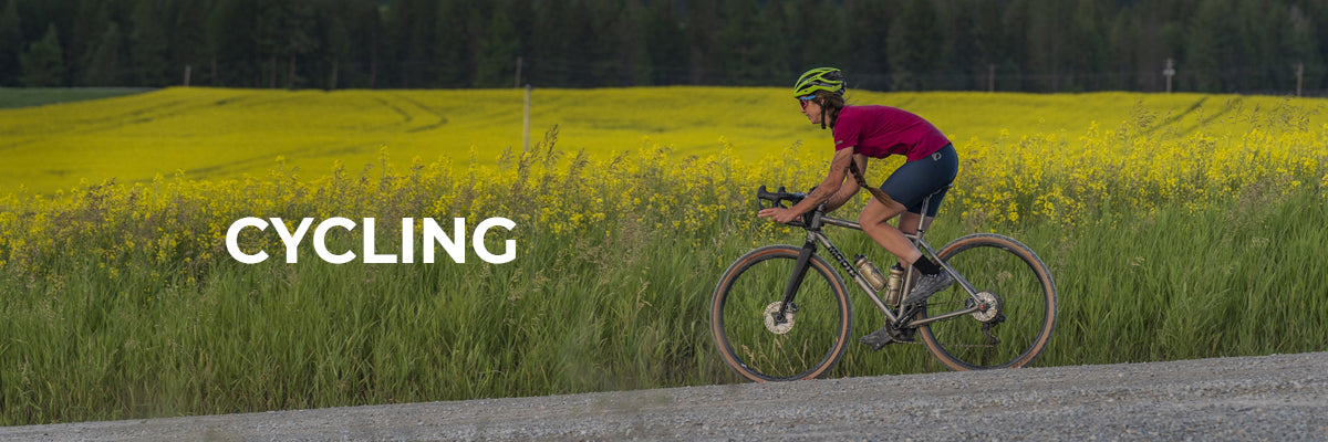 Swiftwick Cycling Header Image, Man cycling by field
