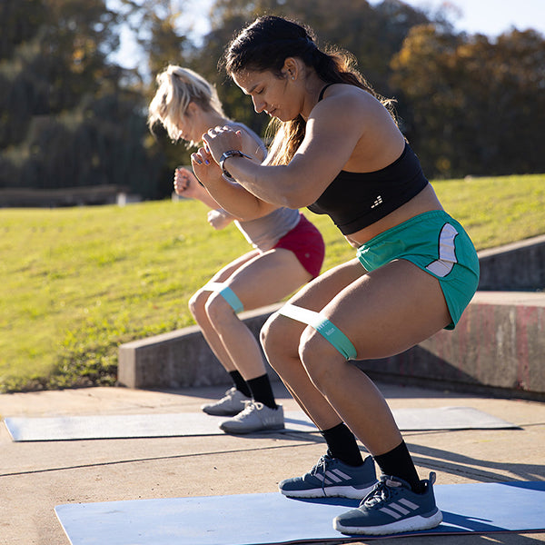 Two women doing squats with resistance bands