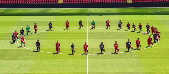 Liverpool players kneel together at Anfield to show support for George Floyd