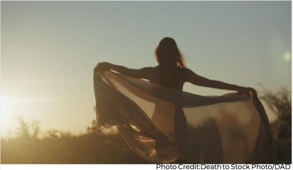 Woman embracing the sunset in the desert connecting with nature for spiritual self-care