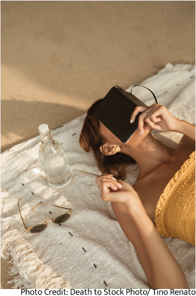 Woman laying on blanket with sun glasses, water, and a book engaging in financial self-care