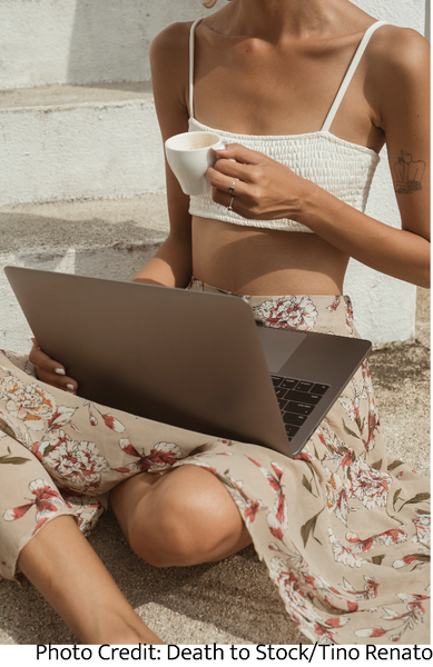 Woman sitting with a laptop in her lap and drinking coffee while budgeting her money as part of financial self-care