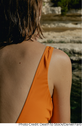 Woman in orange swimwear sitting at the beach for summer vacation