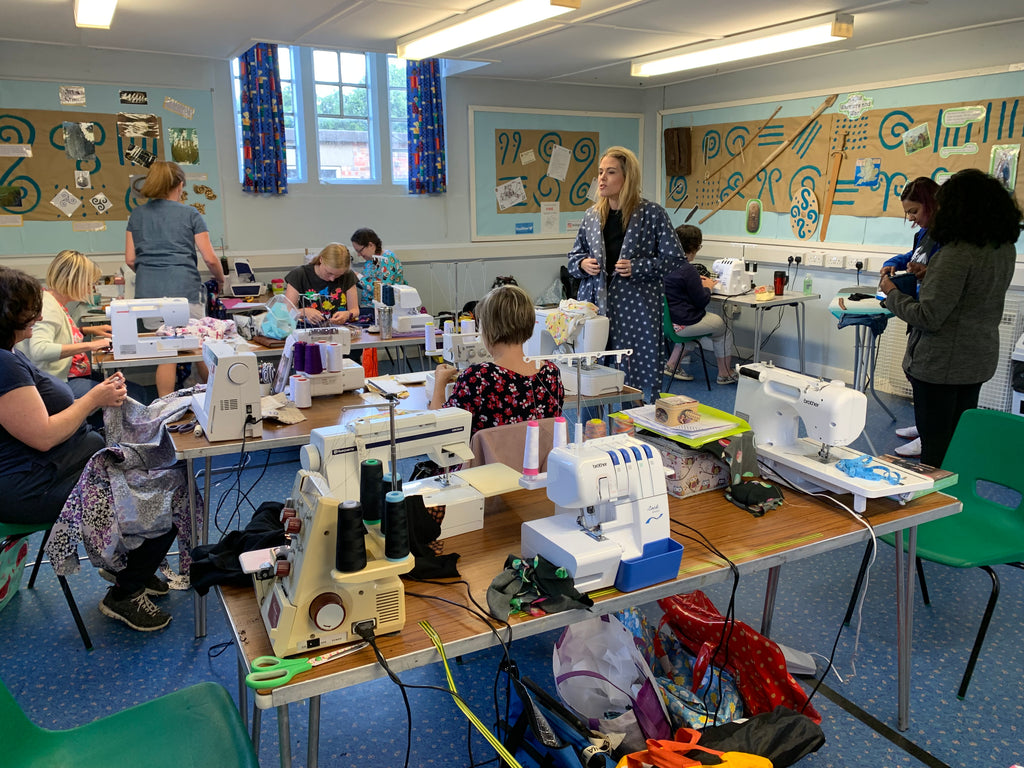 A room full of sewing machines and people talking