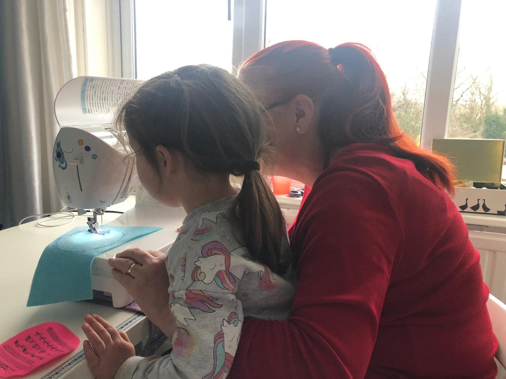 adult and child sewing at a sewing machine