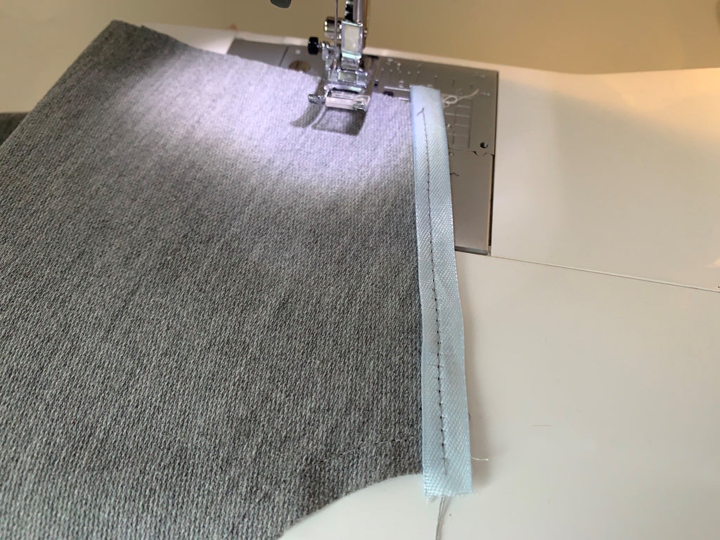 Sewing machine with grey jersey and ribbon