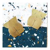 brass earrings on a terrazzo background