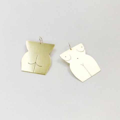 brass earrings in the shape of a front and back nude body