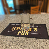 "A Black Bar Runner Mat that says, ""Speck's Pub, Come Early, Stay Late"" with an empty beer mug on it."