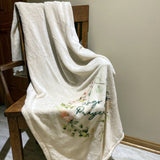Hugs and Prayers blanket draped on a chair