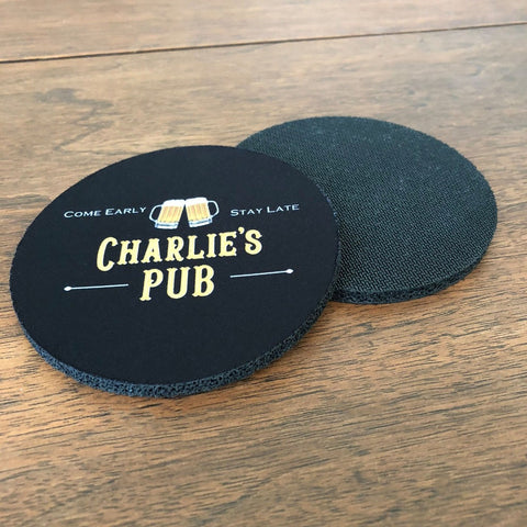 "A pair of black fabric coasters with beer mugs that say, ""Charlie's Pub- Come Early- Stay Late"""