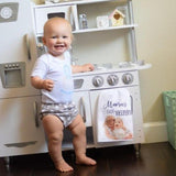 A baby playing in a play kitchen area with a Mama's Little Helper Tea Towel with her photo on it.