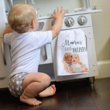 A small child playing in the kitchen with a personalized dish towel with her photo on it hanging beside her.