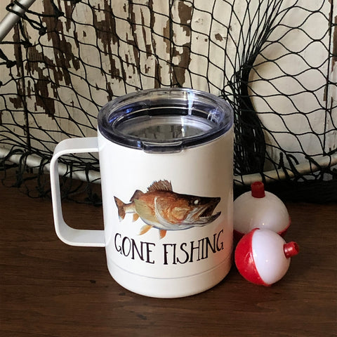"White travel mug with a walleye fish on the front that says, ""Gone Fishing"", sitting on a table by a couple of bobbers and a fishing net."