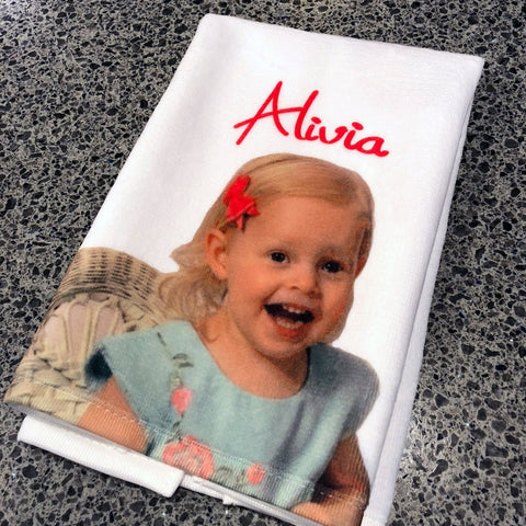 Small Guest Towel with a photo of a smiling child with a bow in her hair, personalized with her name on it.