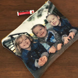 A gold zippered makeup bag featuring a photograph of 3 children printed on it