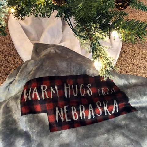 "Gray Plush Fleece Blanket with ""Warm Hugs From Nebraska"" on a red and black buffalo pattern Nebraska shape."
