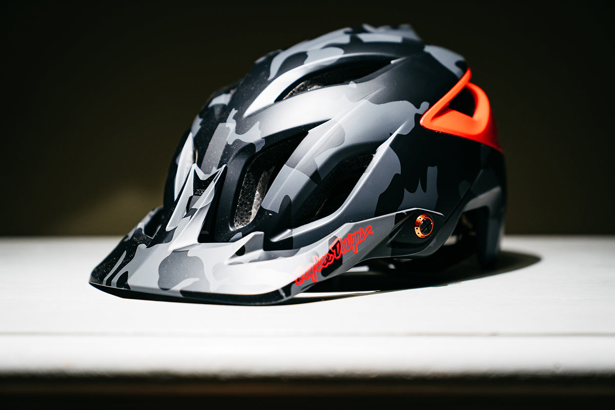 Studio photograph showing the Troy Lee Designs A3 helmet in grey and red at a three quarter angle