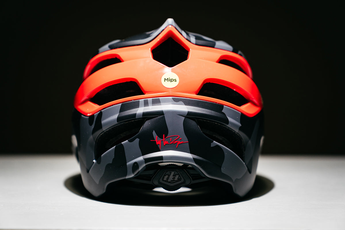 Studio photograph of the Troy Lee Designs A3 helmet in grey and red shot from behind to show the MIPS logo