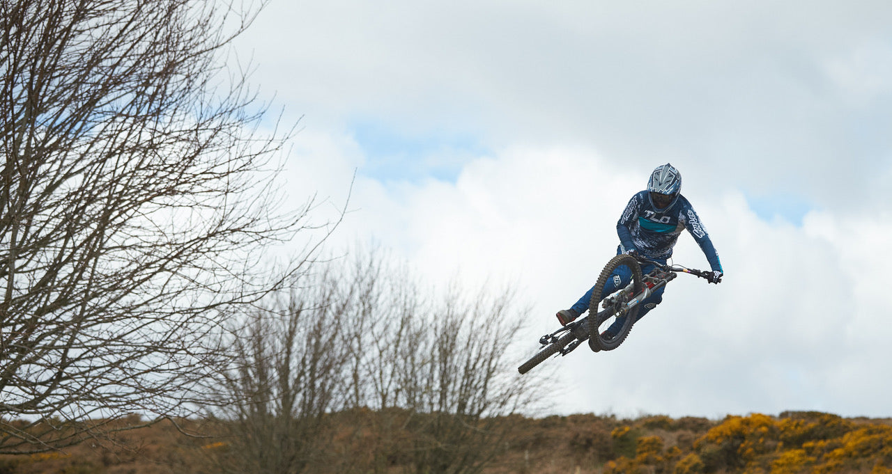 Dan Wolfe wearing TLD doing a jump on his mountain bike with trees and sky in the background